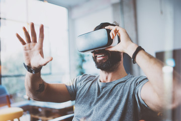 Young bearded man wearing virtual reality glasses in modern interior design coworking studio. Smartphone using with VR goggles headset. Horizontal,flares effect, blurred background.