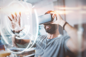 Concept of digital screen,connection and interfaces.Beraded hipster enjoyingvirtual reality glasses in modern design home studio.Smartphone use with VR goggles headset.Horizontal,flare,blurred.