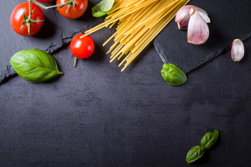 Food ingredients for Italian spaghetti on black stone slate background with much copy space of your project.