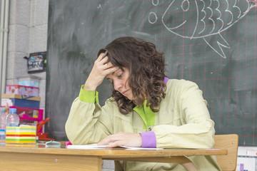 Tired teacher in classroom..