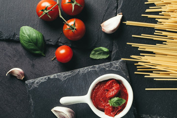 Food ingredients for Italian spaghetti on black stone slate background. Vegetarian version of pasta.