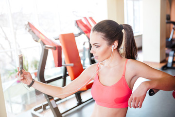 Woman athlete taking selfie and listening to music in gym