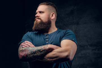Bearded male with tattooed crossed arms.