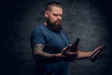 Bearded man holds the beer bottle.