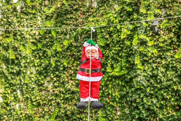 Santa Claus hanging on a white rope in the garden
