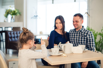 family, parenthood, technology people concept - close up of happy mother, father and little girl having dinner, kid taking photo by smartphone at restaurant