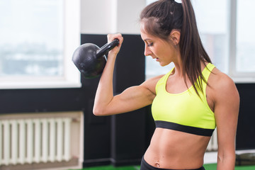 young fit woman doing exercises lifting kettlebell, working out biceps, triceps, back muscles
