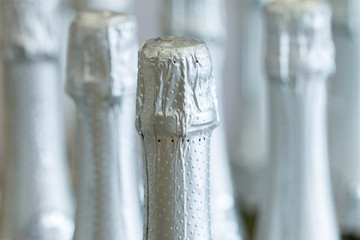 Silver champagne bottle necks and top caps at standing the light background in liquor store.