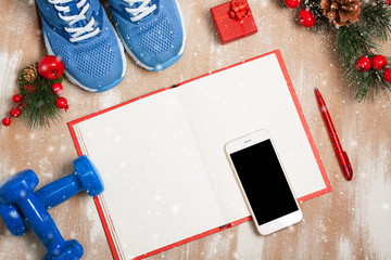 Christmas sport composition with sport shoes, dumbbells, noteboo