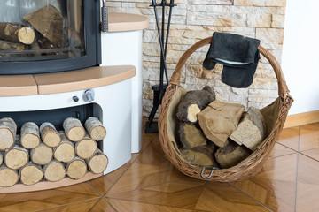 Feuerholz in einem Korb vor dem Kaminofen