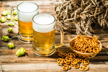 Wheat spikelets with two mugs of beer with hops, pretzels on wooden table