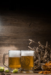 Cups beer, hops, pretzels,spikelets on empty wooden background