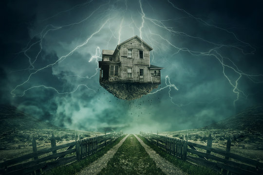 Rapture surreal concept. Ghost house ripped from the ground flying above a country road in a stormy day with lightnings in the sky.