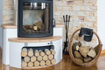 Feuerstelle mit Kaminofen und Holzkorb