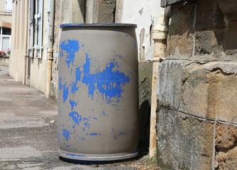 old blue plastic barrel at th street