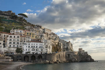 Postcard view of the beautiful town of Amalfi in the morning light. Gulf of Salerno, Campania, Italy. Blue sky background with clouds