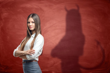 Young businesswoman is casting shadow of devil on rusty orange wall behind her.