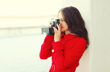 Young woman photographer takes picture on the vintage camera in