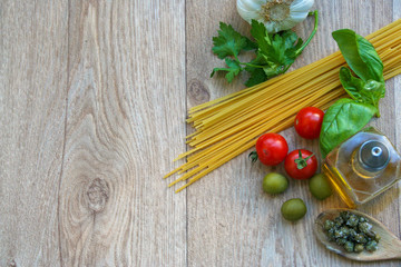 Ingredients for italian spaghetti alla puttanesca, with olive, tomatoes  and capers