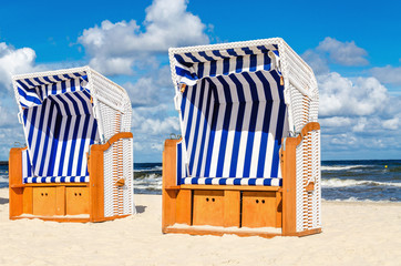 Wicker chairs on sandy Kolobrzeg beach by Baltic Sea, Poland