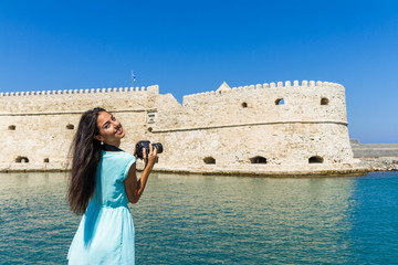 Young stylish woman photographing Rocca A Mare Heraklion, Crete, Greece