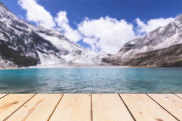 Wooden board empty table in front of blurred background. Perspective brown wood over lake in snow mountain for mock up  display or montage your products, vintage.