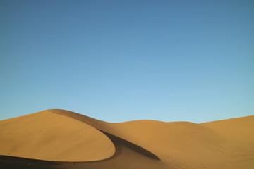 Deserto com grande duna de areia e céu azul