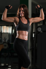 Biceps Pose Of A Young Woman In Gym
