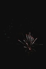Shiny natural fireworks on dark black sky background with a litt