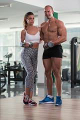 Young Couple Doing Exercise For Biceps With Dumbbells