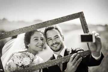 selfie of newlyweds on a country road through a frame