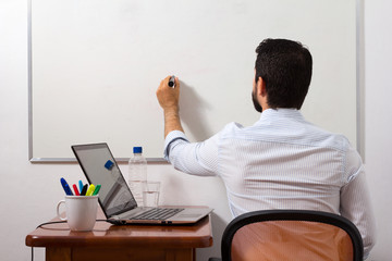 Home office, man writing in white board