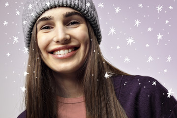 Beautiful pretty young woman smiling, close-up portrait. Winter mood. Happy face emotions. Violet background with snowflakes