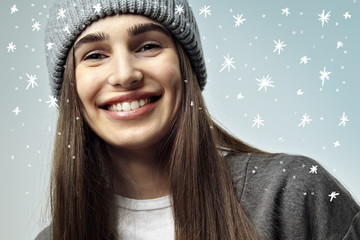 Beautiful pretty young woman smiling, close-up portrait. Winter mood. Happy face emotions. Green background with snowflakes
