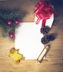Christmas card: blank, vintage rural gift and Christmas tree branch on wooden background with gift