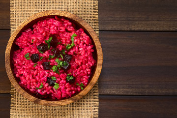 Beetroot risotto prepared with beetroot puree, roasted beetroot pieces and parsley on the top, photographed overhead on dark wood with natural light (Selective Focus, Focus on the top of the risotto)