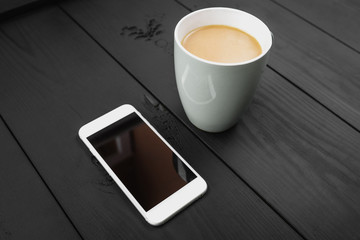 Cup of coffee and smart phone with white screen on the black wooden background.