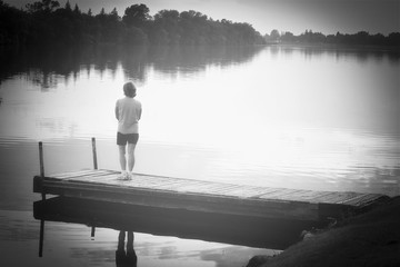 horizontal black and white image of a caucasian woman standing on the pier and looking at the lake with a light fog in the air in the summer.
