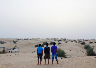 Foto op Canvas Marokko A group of 3 young Indian men watching the sunset at a desert safari camp in Dubai, UAE