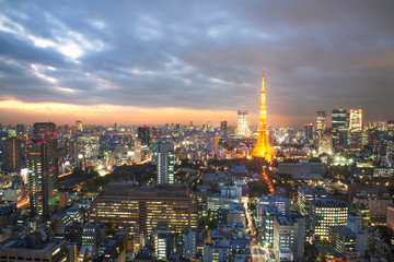 Illuminated Tokyo Tower amidst cityscape with sunset sky