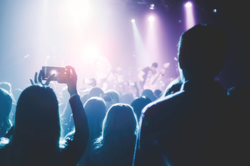 Female hands holding their smartphone and photographing concert