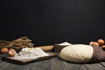 Fresh dough with flour and eggs on wooden table