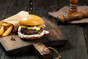 Tasty grilled beef burger with potatoes on rustic wooden table