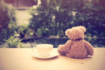Alone teddy bear sit back  with coffee cup on wooden floor with