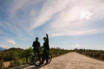 Two young men enjoy with mountain bike driving by countryside