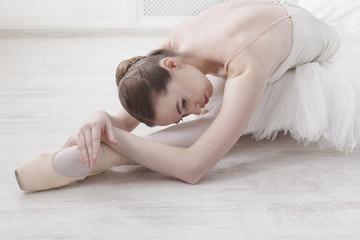 Graceful Ballerina stretching, ballet background