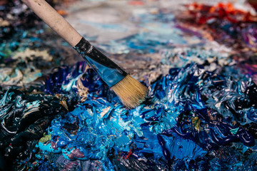 Colorful painter palette and wood brush, cropped image. Place for text