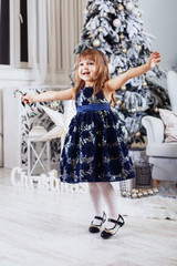 The little girl in a dress congratulates the holidays.
