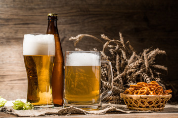 Mug, glasse, bottle of beer with foam close up