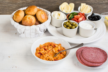 Traditional Turkish breakfast: egg, toast, pogaca pasties, vegetables, cheeses, olives and halal turkey salami, selective focus; copy space for text